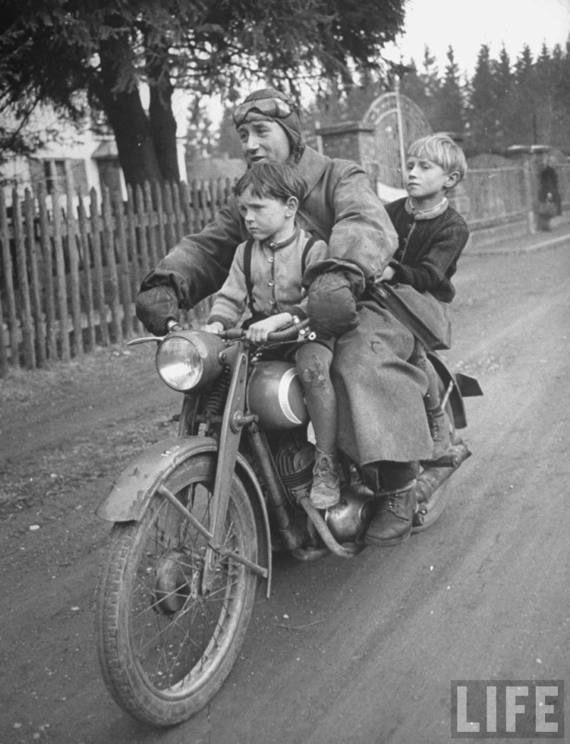A man riding a motorcycle with his two children. Photograph by Walter Sanders. Munich, Germany, May 1949