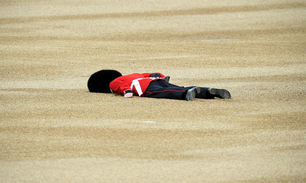LONDON, ENGLAND - JUNE 11:  A member of the Queens Guard collapses during the Trooping the Colour, this year marking the Queen's 90th birthday at The Mall on June 11, 2016 in London, England. The ceremony is Queen Elizabeth II's annual birthday parade and dates back to the time of Charles II in the 17th Century when the Colours of a regiment were used as a rallying point in battle.  (Photo by Stuart C. Wilson/Getty Images)